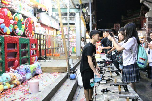 台湾(台北)の士林夜市の射的屋で制服姿の女子高生が拳銃を構える