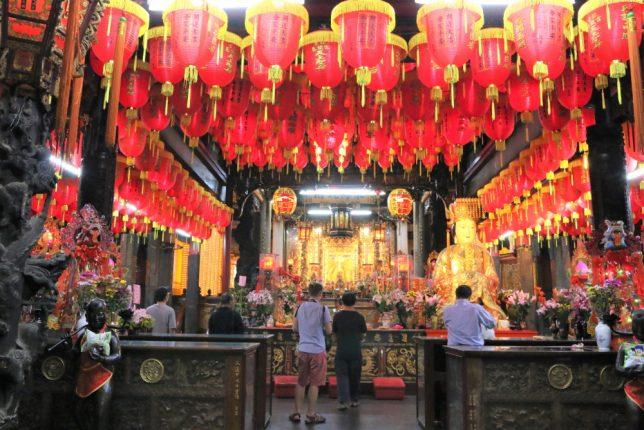 士林夜市の寺、士林慈誠宮の祭壇にお参りする観光客