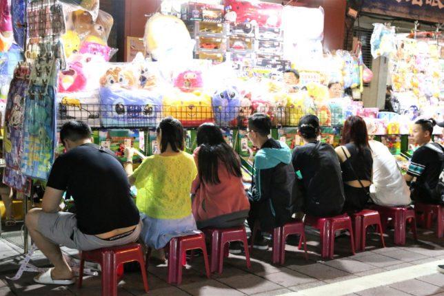 寧夏夜市の通りでパチンコで遊ぶ人々