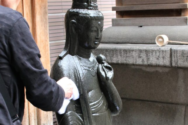 巣鴨(高岩寺)のとげぬき地蔵。体の悪い所に水をかけてタオルで拭いているところ