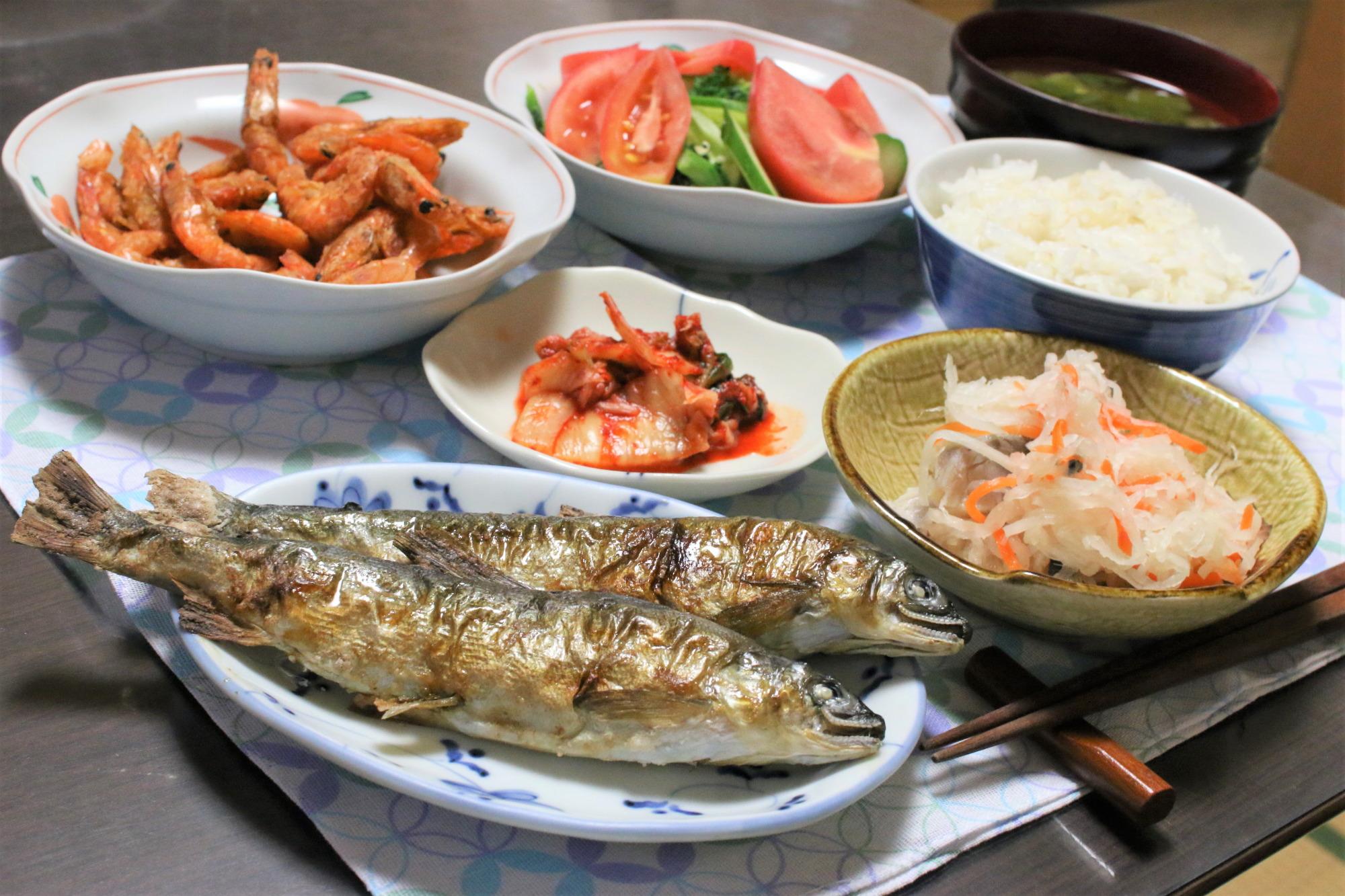 鮎の塩焼きと小エビの素揚げ、キムチ、なますなどの晩ごはんの献立