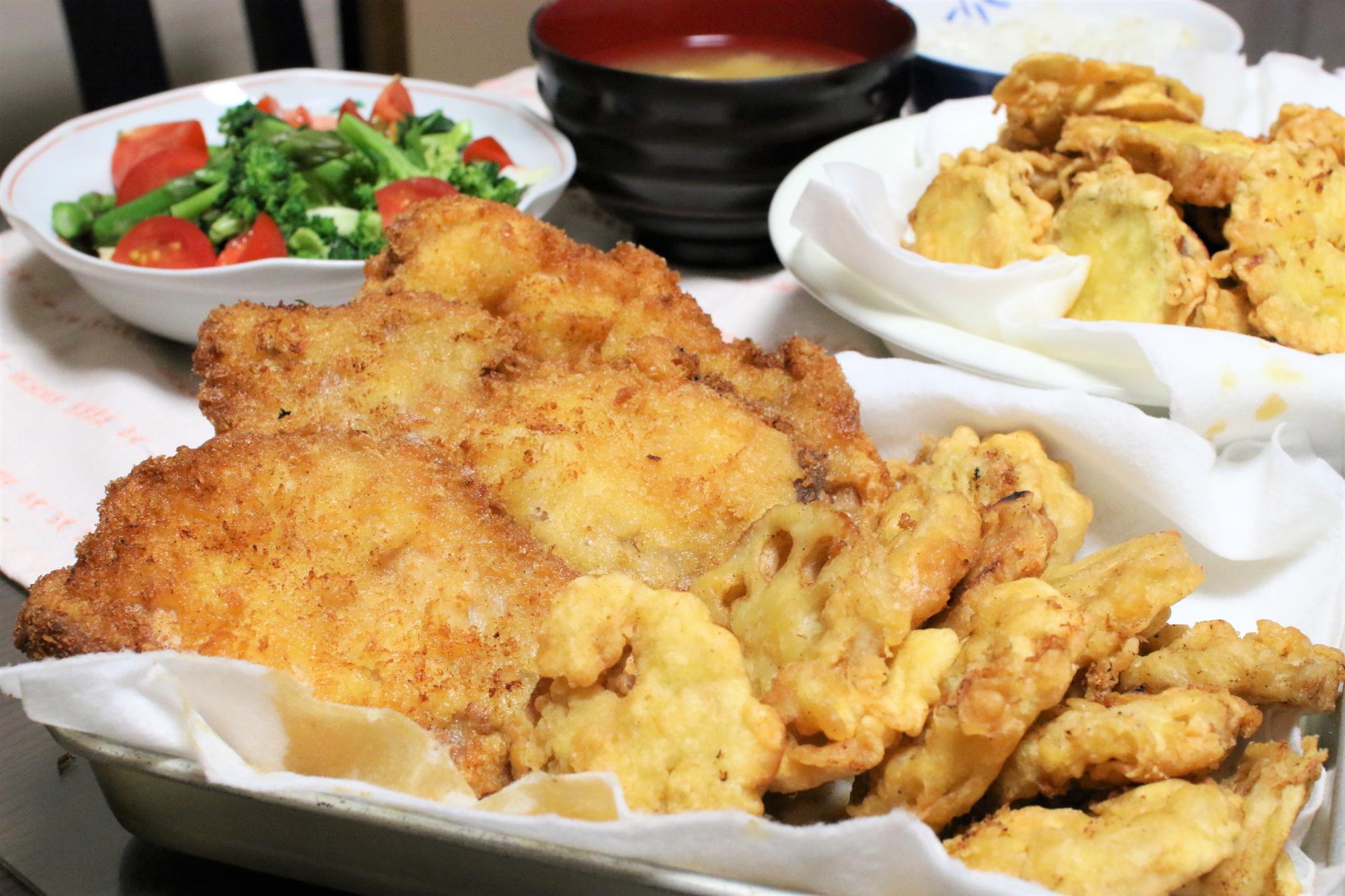 巨大なとんかつ、さつまいもとレンコンの天ぷらなど、おばあが作った晩ごはんメニュー