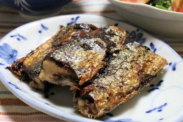 二つに切った秋刀魚を2尾、焼いたもの。フライパンで焼いたので表面が揚げたようになっている