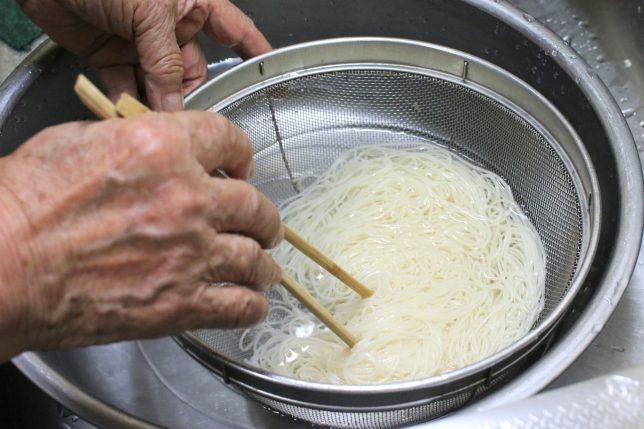 茹でた三輪素麺をおばあが水で洗って冷ます。
