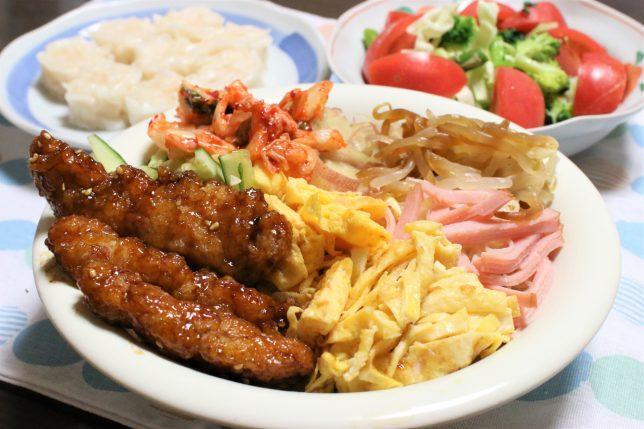 揚げた鶏肉の甘酢あえ、キムチ、茹でもやしなどの具材をのせたそうめん。