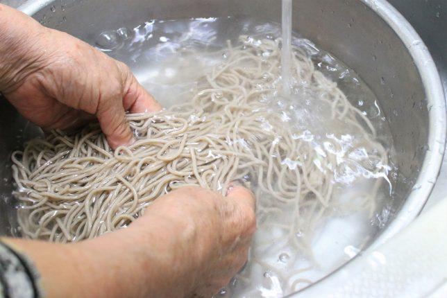 茹であがった「山形のとびきりそば」をおばあが冷水で洗っているところ
