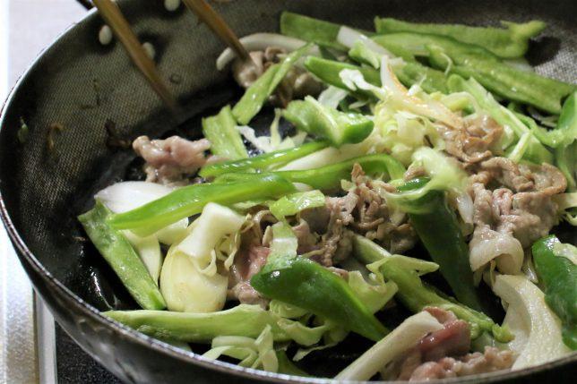 やきそばの具材(牛バラ肉と玉ねぎ、ピーマン、キャベツ)を、おばあが炒めているところ