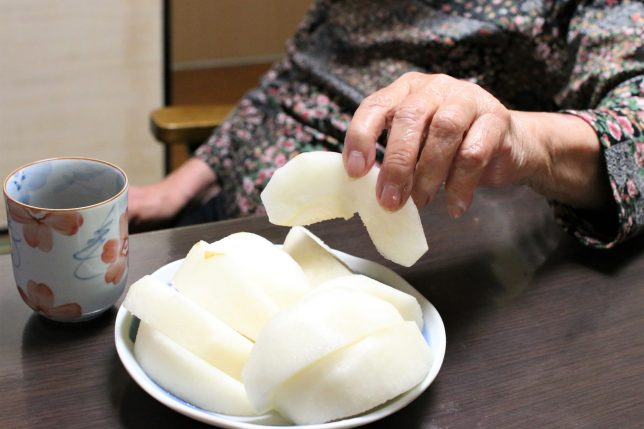 梨を手づかみで食べるおばあ