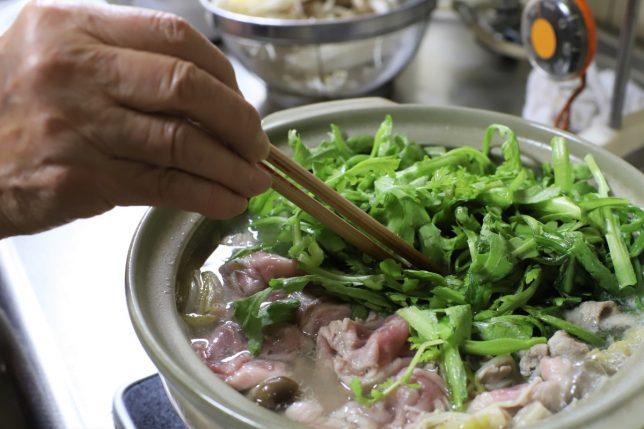 土鍋に投入した春菊を、おばあが菜箸で押さえているところ