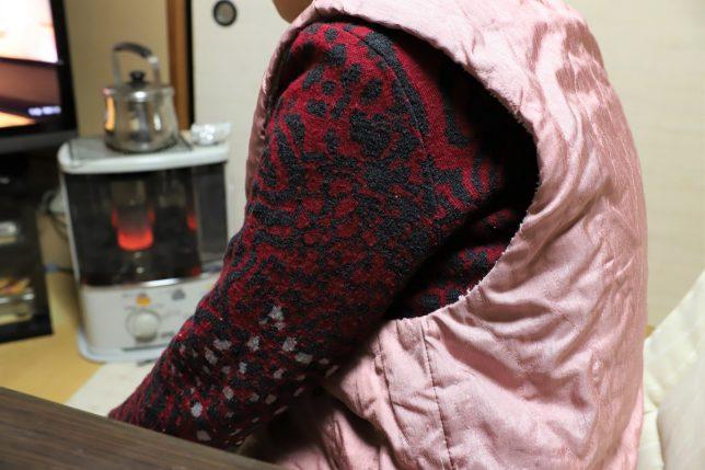 おでんを食べ終わった後、灯油ストーブの前で休むおばあ
