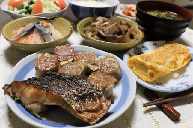 知らん魚の焼いたんや冷凍シュウマイ、玉子焼きなど、おばあがつくった晩ごはんのメニュー