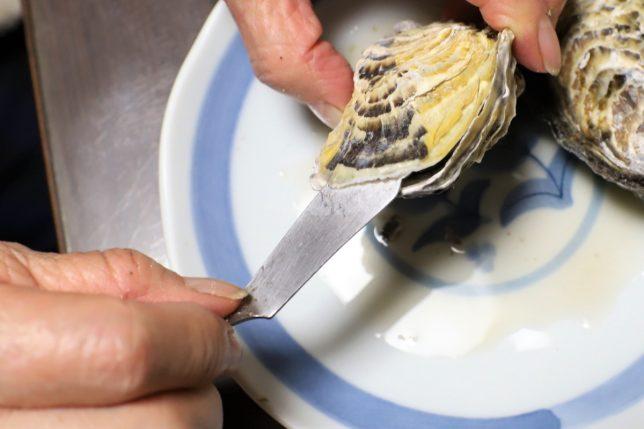 蒸し牡蠣の殻にバターナイフを差し込んで開けるところ