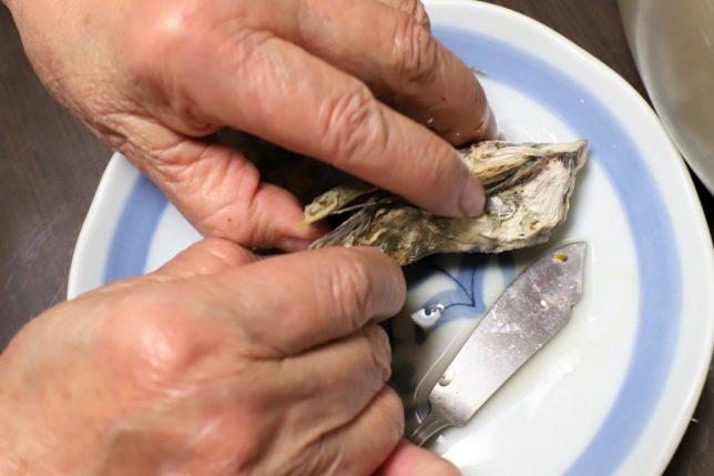 蒸し牡蠣を手で開けているおばあ