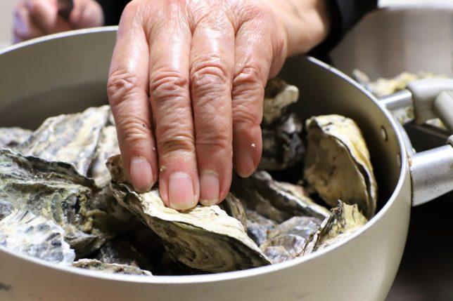 蒸した牡蠣をつかむおばあの手