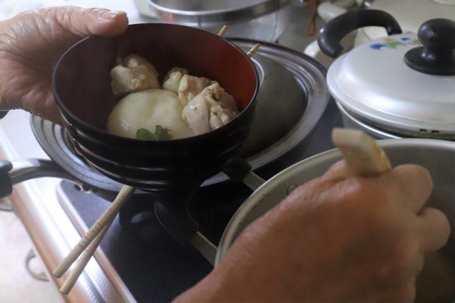 丸餅入りの雑煮をお椀につぐおばあ