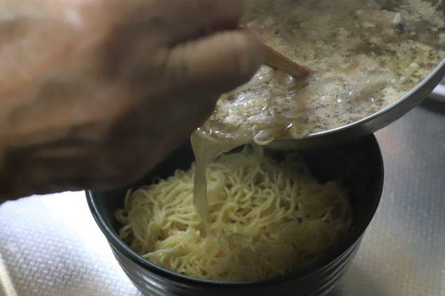 「マルちゃん正麺 豚骨味」のスープを麺にかけているところ