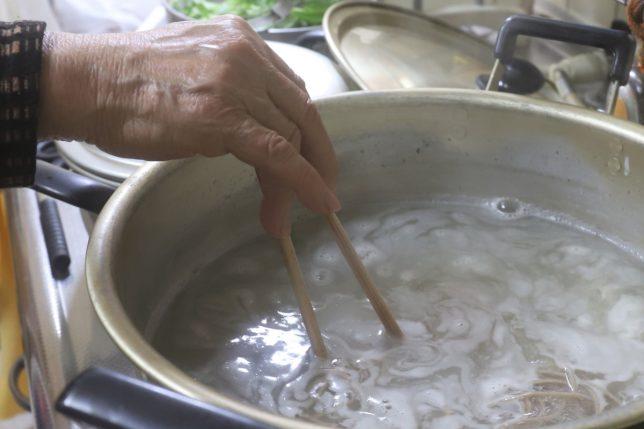 恩地食品の藪蕎麦(年越しそば)を鍋で茹でるおばあ