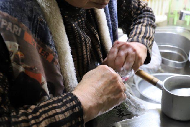 恩地食品の藪蕎麦(年越しそば)の袋を開けるおばあ