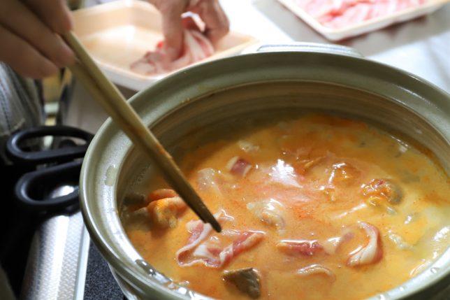 ピリ辛とり野菜みそ鍋に肉を投入する祖母(おばあ)