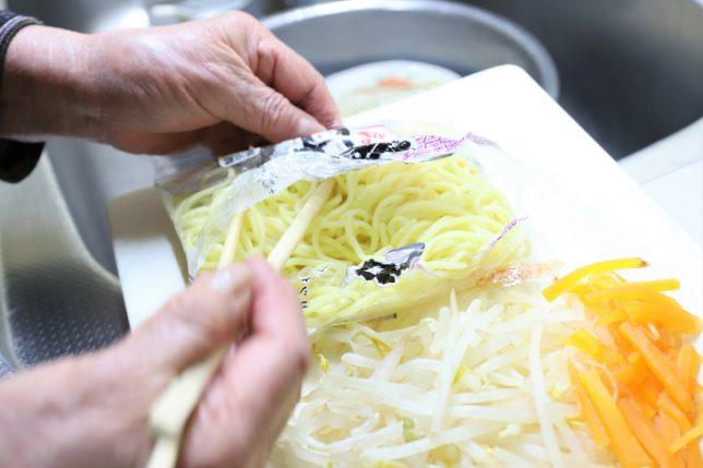 ラーメンの麺の袋を開ける祖母(おばあ)と刻んだ具材