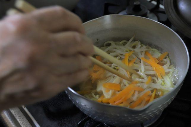 鍋にラーメンと野菜を入れて祖母が菜箸で混ぜているところ