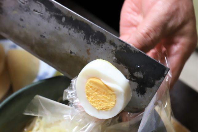 祖母(おばあ)が茹で玉子を包丁で切っているところ