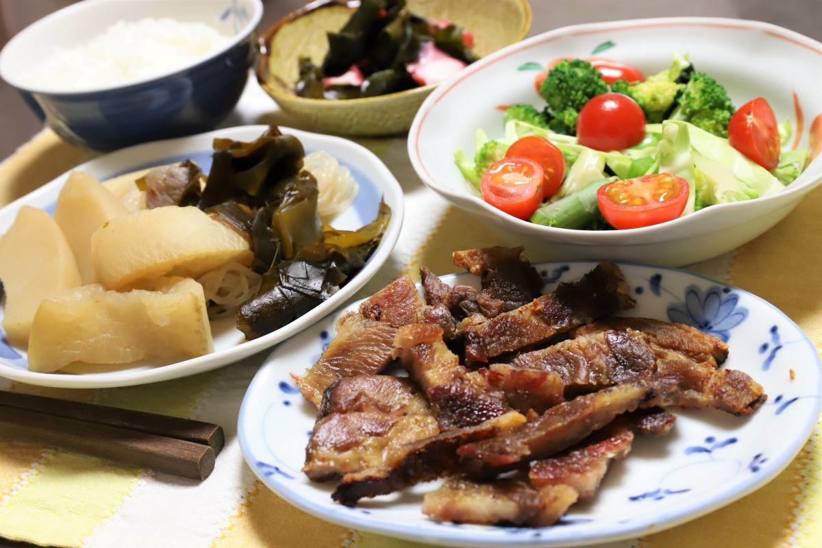カリカリに焼いた豚肉やワカメと大根の煮物など、祖母(おばあ)がつくった晩ごはんのメニュー