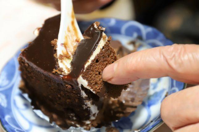 祖母が手を使って食べているガトーショコラ