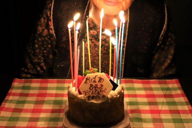 84歳の誕生日ケーキに立てたろうそくの火を吹き消すおばあ