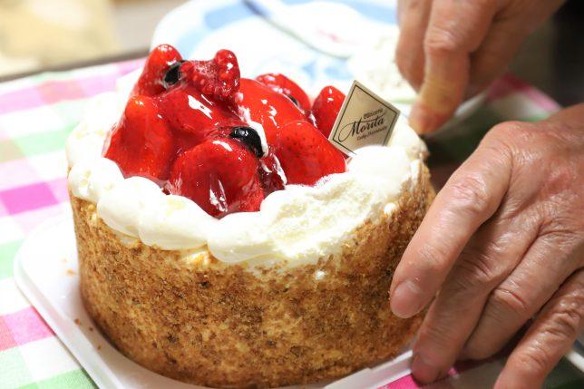 バターナイフで誕生日ケーキを切るおばあ