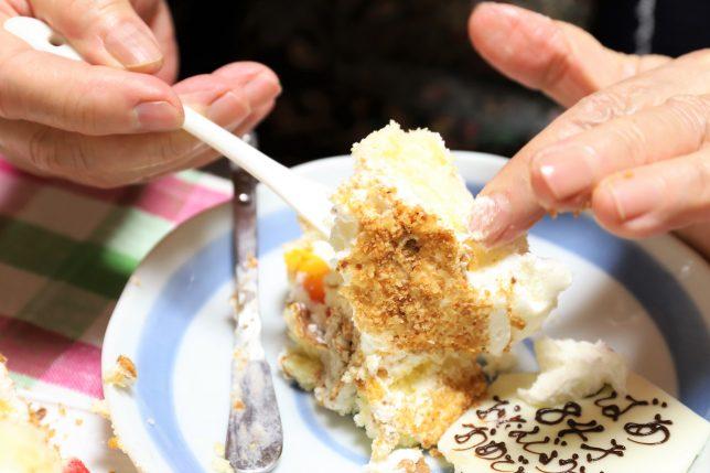 つぶれた誕生日ケーキを手で食べるおばあ