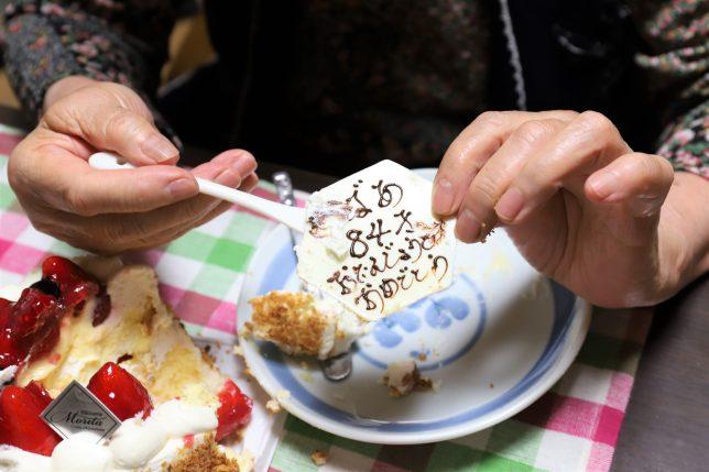 誕生日ケーキのチョコレートを食べるおばあ