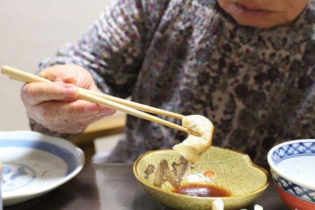 一口餃子をタレにつけて食べる祖母(おばあ)