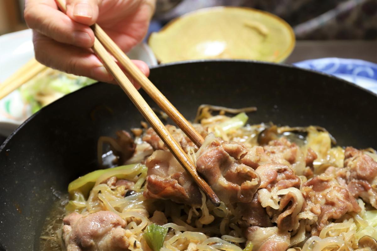 すき焼きの豚肉を菜箸でつまむ祖母(おばあ)