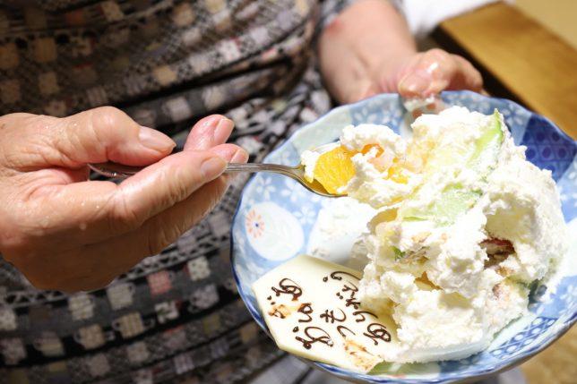 敬老の日のフルーツケーキを抱えて食べる祖母(おばあ)