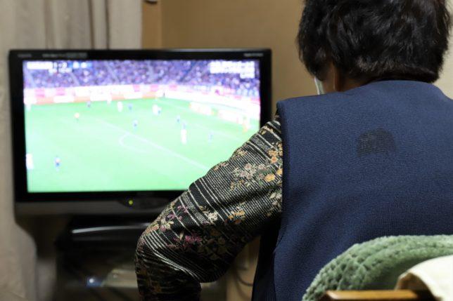 日本代表とウルグアイ代表のサッカーの試合をテレビで見る祖母(おばあ)