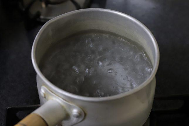 片手鍋の中でお湯が沸騰しているところ