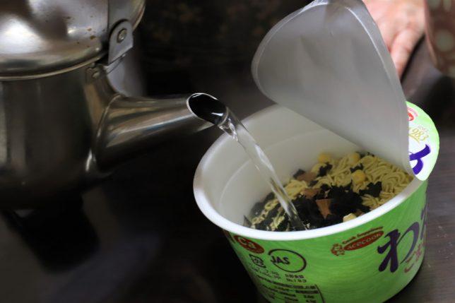 エースコックの「わかめラーメン」にお湯を注いでいるところ