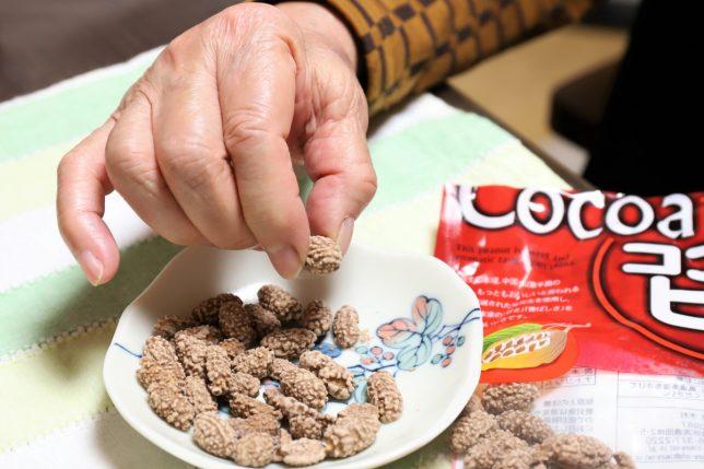 ココアピーを摘まむ祖母(おばあ)の手
