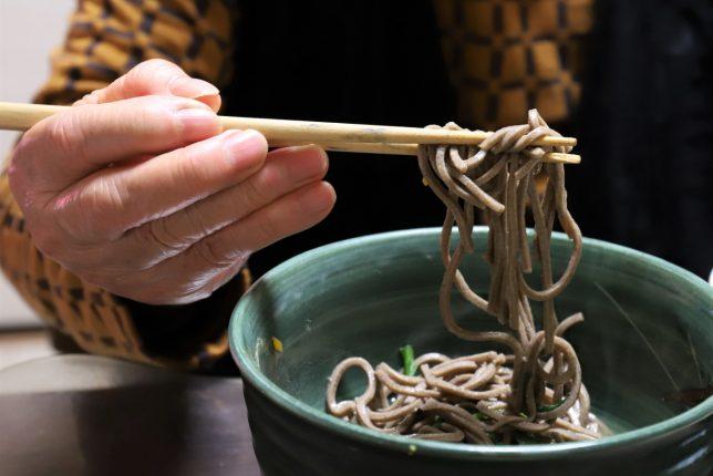 年越しそば(藪蕎麦)を箸で掴んでいる祖母(おばあ)