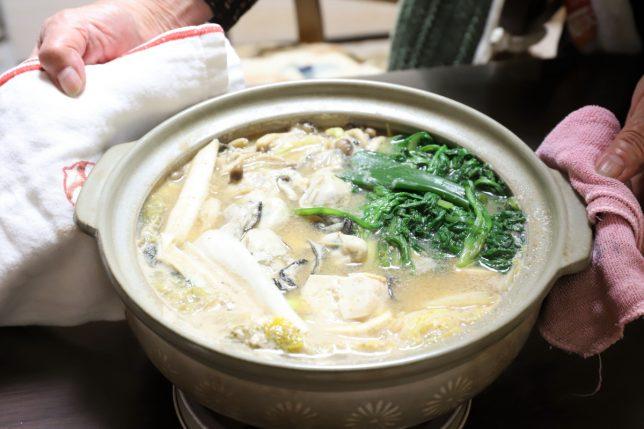 土鍋に入った味噌味の牡蠣鍋を運んできたところ