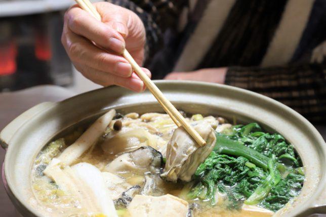 土鍋に入った牡蠣鍋の牡蠣を箸でつまんでいるところ