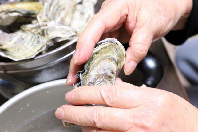 手づかみで牡蠣の殻を開けるところ
