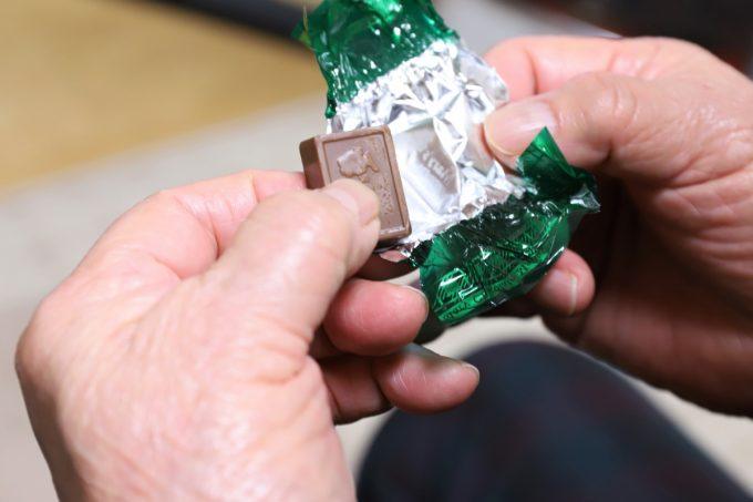 チョコレートを手でつまんで食べようとしているところ