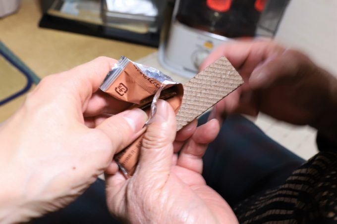ウエハースチョコを祖母(おばあ)に手渡しているところ