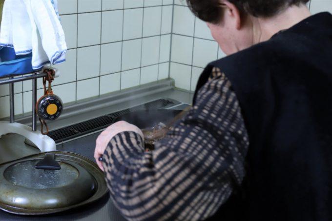 鶏肉のすき焼きを作っている祖母(おばあ)の後ろ姿