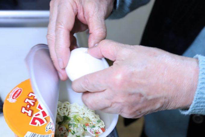 インスタントのカップ麺の上で生タマゴを割って入れているところ