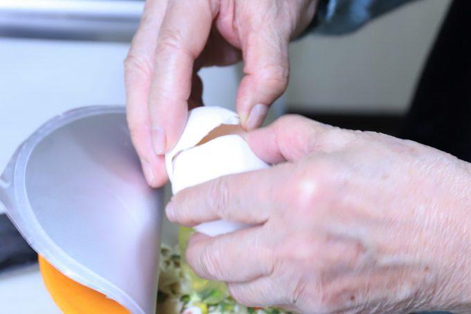 エースコックのワンタンメンに生卵を割り入れているところ