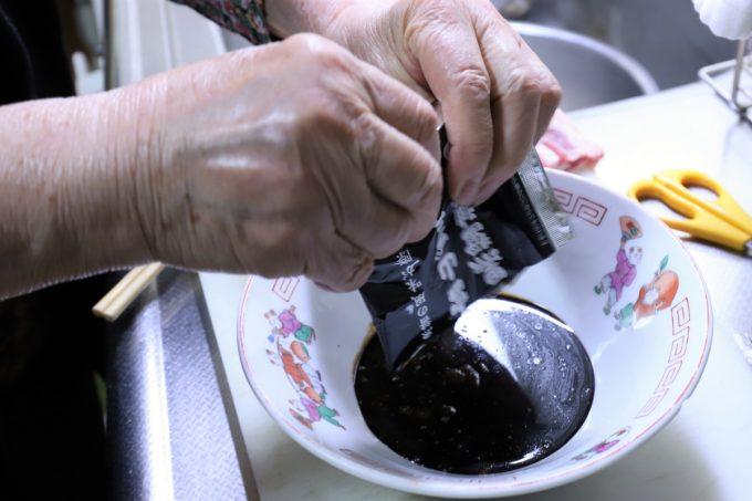 麺屋いろは「富山ブラックラーメン」の袋入りスープを、丼ぶりに入れているところ
