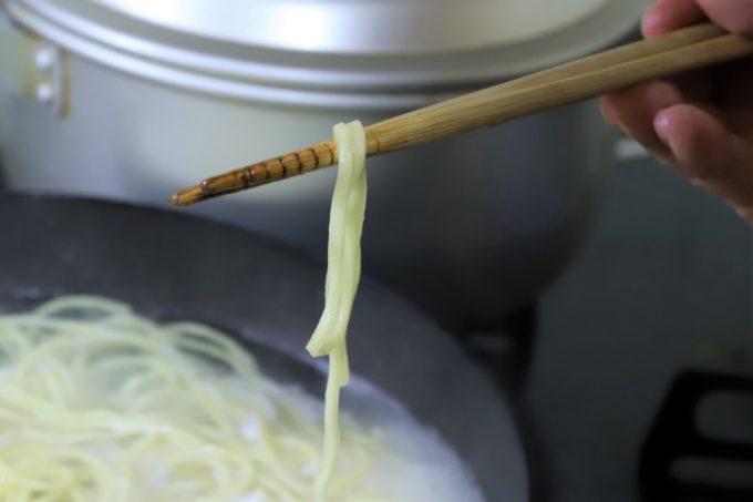 麺屋いろは「富山ブラック 黒醤油ラーメン」(インスタント)の麺を箸で摘まんでいるところ